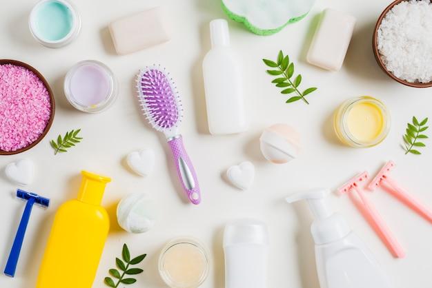 Produtos de cosméticos de spa com navalha e escova de cabelo em fundo branco