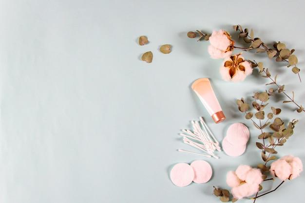 Produtos de cosméticos spa - pote de creme, folhas de eucalipto, flores de algodão, almofadas, bastões de orelha na luz de fundo. produto de beleza natural da pele orgânica no mínimo, banner. vista plana, vista superior, cópia espaço