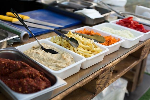Produtos de cozinha ao ar livre para cozinhar falafel em pratos sobre uma mesa de madeira.