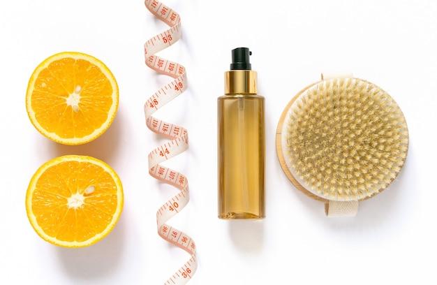 Produtos de cuidado anticelulite. escova para massagem a seco e óleo no fundo branco, vista superior.
