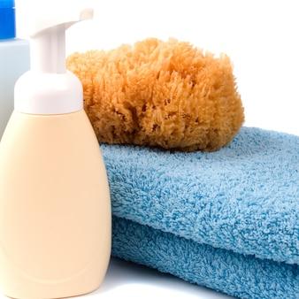 Produtos de cuidado de corpo e toalha no fundo branco