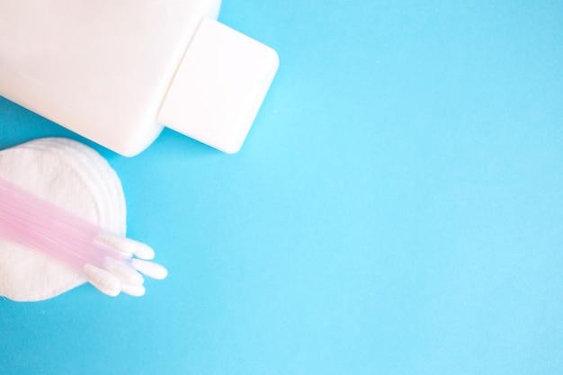 Produtos de cuidado pessoal. garrafa branca, varas da orelha, almofadas de algodão no fundo azul. spa de cópia