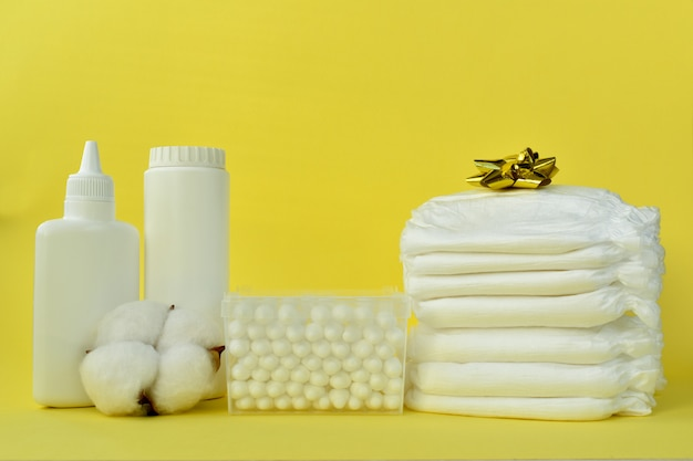 Produtos de cuidados com o bebê em um fundo amarelo.