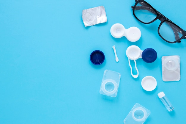 Produtos de cuidados dos olhos em fundo azul com espaço de cópia