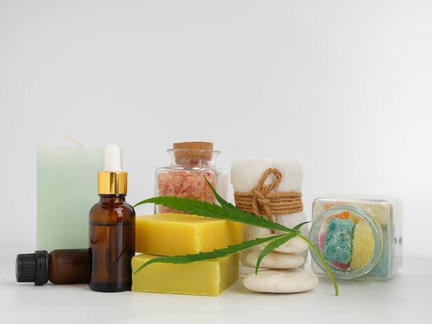 Produtos de extrato de cânhamo de spa com sabonete de folha de cannabis, loção de óleo cbd e pedra branca de sal rosa do himalaia em fundo branco