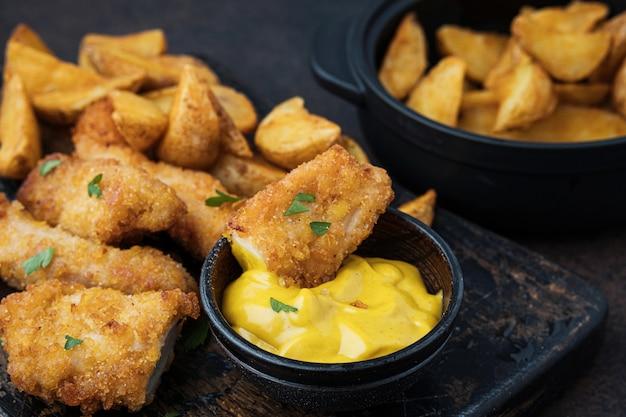 Produtos de fast food: frango com molho e batatas