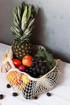 Produtos de frutas e vegetais em uma sacola ecológica em uma mesa de madeira branca