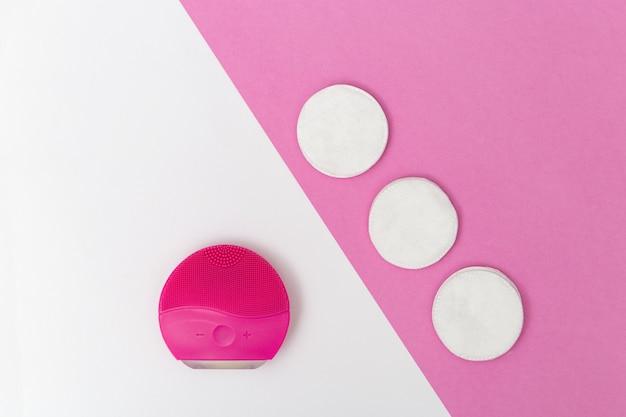 Produtos de higiene e beleza femininos, pincel de rosto elecrtico vermelho e almofadas de algodão em papel branco e rosa
