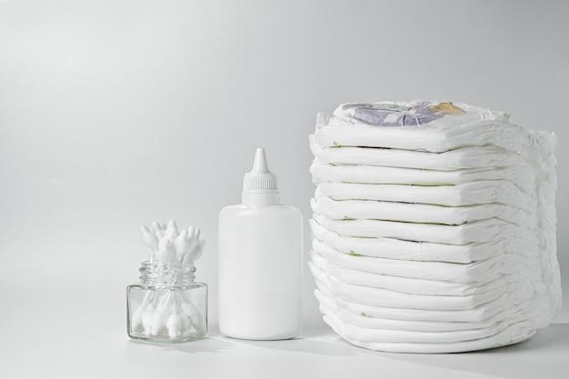 Produtos de higiene e cuidado corporal para o bebê. fraldas e calcinhas, creme, chupeta e talco.