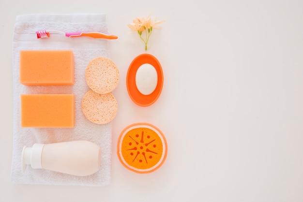 Produtos de higiene pessoal laranja na toalha branca