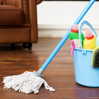 Produtos de limpeza de casa no balde azul no chão de madeira