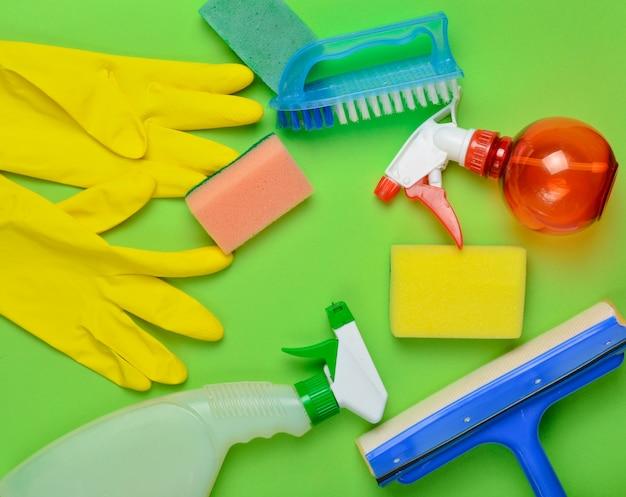 Produtos de limpeza doméstica. esfregona, esponja, frasco de spray, luvas de látex amarelas, pincel. vista do topo. estilo liso leigo