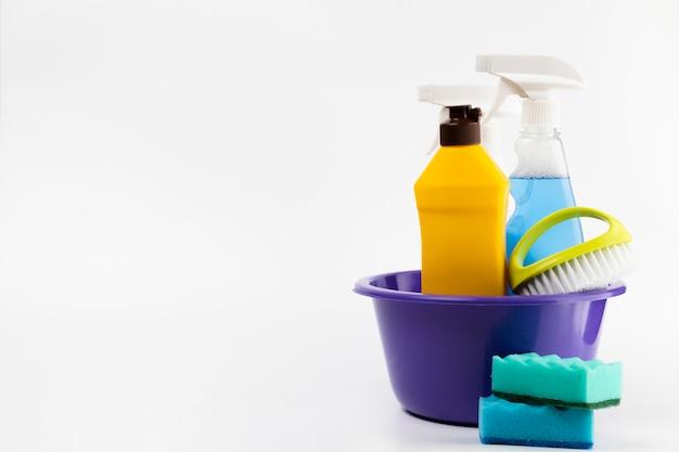 Produtos de limpeza na bacia com esponjas azuis