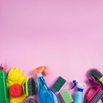 Produtos de limpeza na borda do pano de fundo rosa