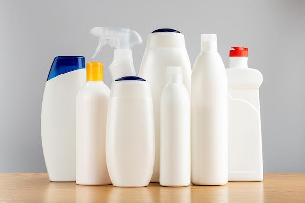 Produtos de limpeza para o cabelo e o corpo e para o banheiro e as janelas. produtos químicos domésticos em uma parede cinza.