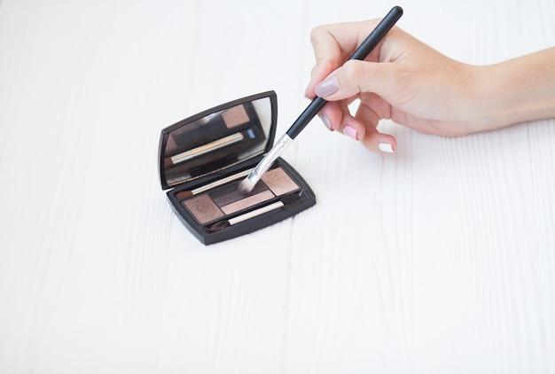 Produtos de maquiagem de paleta de sombras coloridas. sombra de olhos com pincel.