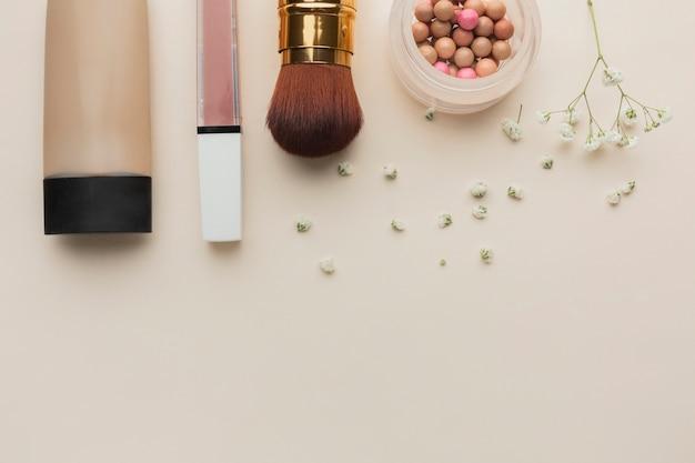 Produtos de maquiagem de vista superior alinhados na mesa