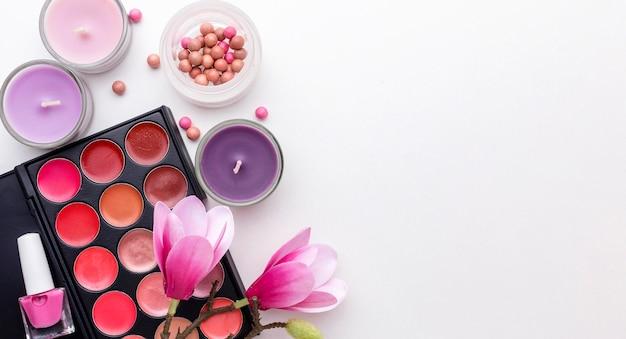 Produtos de maquiagem de vista superior e velas com espaço de cópia
