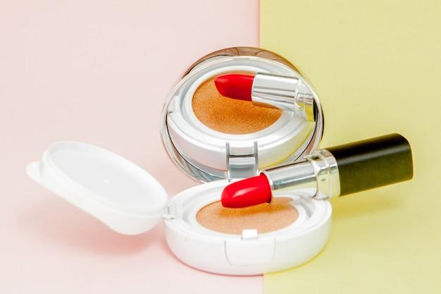 Produtos de maquiagem derramando em amarelo e rosa