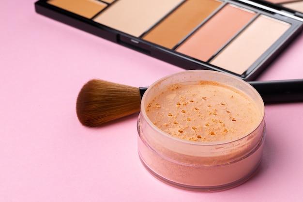 Produtos de maquiagem e pincel em fundo rosa