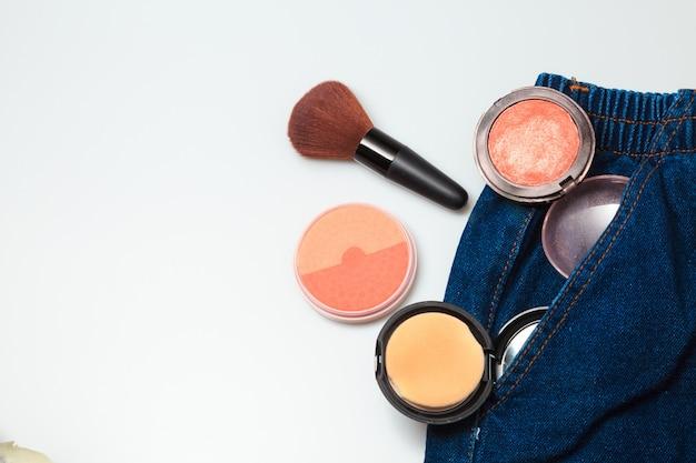 Produtos de maquiagem e produtos de beleza cosméticos derramando fora de jeans de mulher