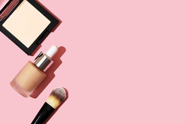 Produtos de maquiagem para o tom de pele. pincel para base, creme bb, pó em uma caixa quadrada em uma vista superior do plano de fundo rosa. cosméticos para maquiador profissional plana leigos. copie o espaço.