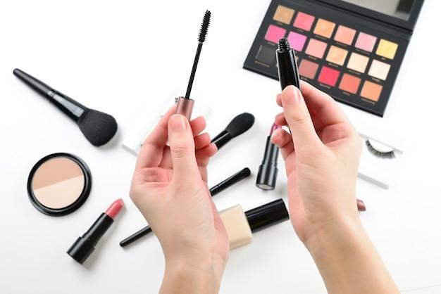 Produtos de maquiagem profissional com produtos cosméticos de beleza, base, batom, sombras, cílios, pincéis e ferramentas. rímel nas mãos da mulher.