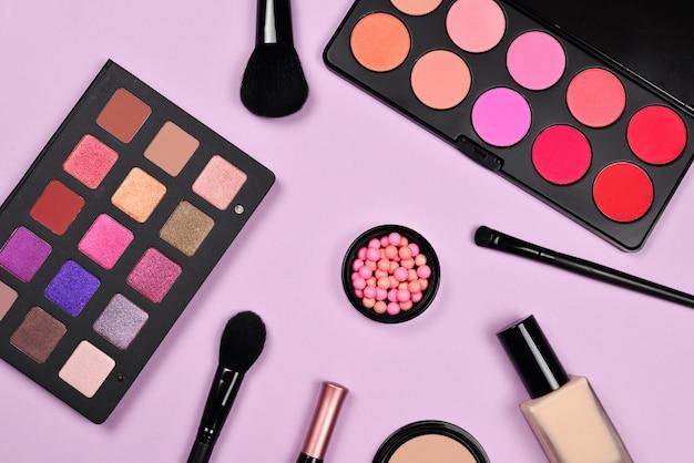 Produtos de maquiagem profissional com produtos cosméticos de beleza, base, batom, sombras, cílios, pincéis e ferramentas.