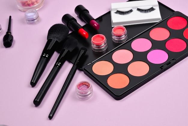Produtos de maquiagem profissional com produtos cosméticos de beleza, blushes, delineador, cílios, pincéis e ferramentas.