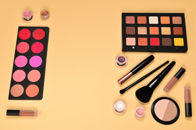 Produtos de maquiagem profissional com produtos cosméticos de beleza, sombras, pigmentos, batons, pincéis e ferramentas em fundo bege. espaço para texto ou desenho.