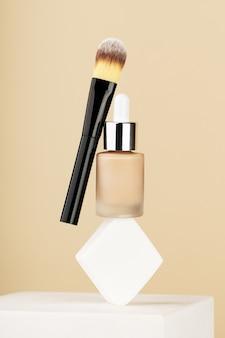 Produtos de maquiagem profissional levitam e se equilibram na esponja branca no suporte. frasco base líquido bb creme, escova acessória de cosmetologia em fundo bege. cosméticos de beleza para uma pele de rosto perfeita.