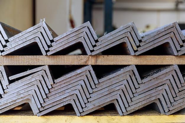 Produtos de metal laminado, perfil em l. uma pilha de cantoneiras de aço em uma fábrica. perfil de metal após corte com serra de fita. l-profil.