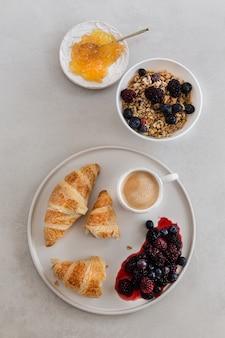 Produtos de pastelaria vista superior na bandeja com uma xícara de café, azeitona, framboesa, geléia de frutas, nozes na superfície branca. vertical