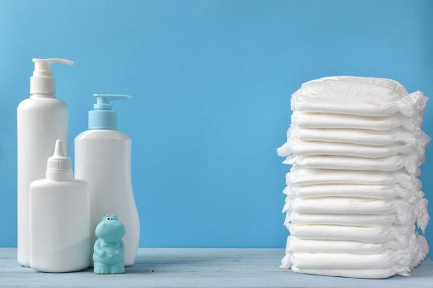 Produtos de puericultura. cosméticos e higiene infantil. cuidado do corpo. modelos de plástico branco de frascos com shampoo ou gel de banho. espaço vazio para o texto.