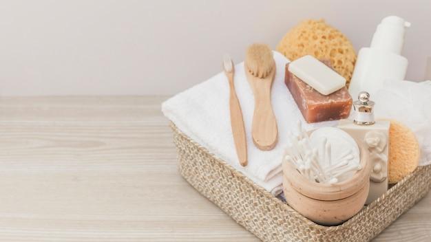 Produtos de spa com escovas e bucha na bandeja no pano de fundo de madeira