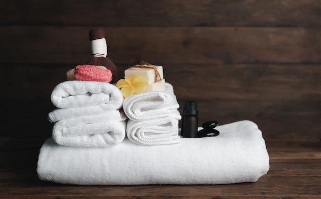 Produtos de spa com toalhas brancas, sabonete orgânico, esfoliante luffa, bola de compressão, pedras pretas e uma linda flor de plumerai sobre fundo de madeira escura