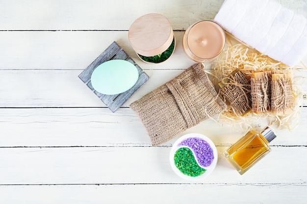 Produtos de spa e banheiro diferentes isolados em fundo de madeira. produtos para tratamentos de beleza e cuidados com o corpo