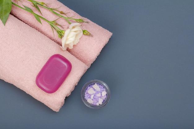 Produtos de spa para cuidados faciais e corporais. sal marinho natural, sabonete caseiro e toalhas cor de rosa com flores em fundo cinza. conceito de spa e cuidados corporais. vista do topo.