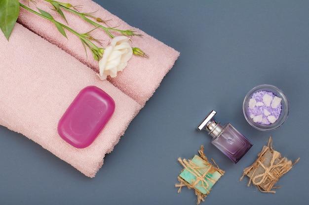 Produtos de spa para cuidados faciais e corporais. sal marinho natural, sabonete caseiro, perfume e toalhas cor de rosa com flor em fundo cinza. conceito de spa e cuidados corporais. vista do topo.