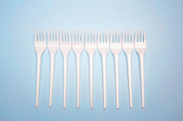 Produtos de uso único de plástico: talheres de plástico, copos em fundo azul brilhante