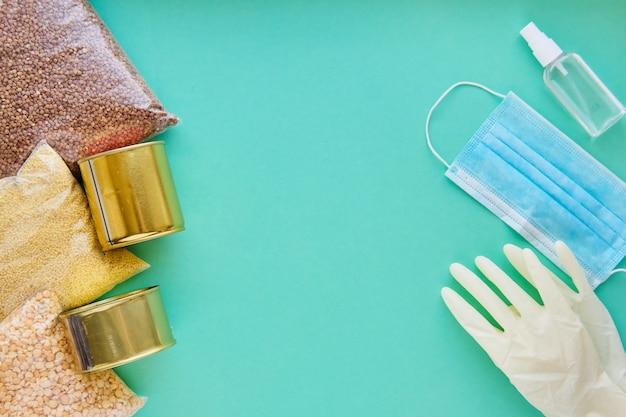 Produtos diferentes e máscara médica e luva em uma mesa azul. o conceito de entrega segura de alimentos durante a quarentena.