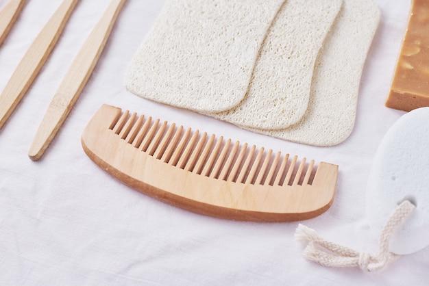 Produtos ecológicos de madeira natural para cuidados com o corpo na vista superior rosa, plana leiga, escovas de dente de bambu, pente de madeira, sabão, esponja e toalhetes naturais, conceito de desperdício zero
