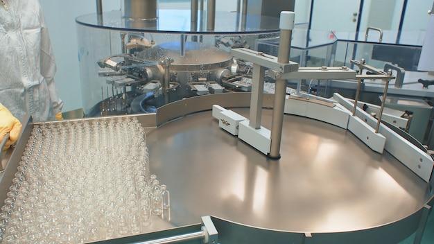 Produtos farmacêuticos. frascos médicos em pé na linha de produção de medicamentos contra vírus