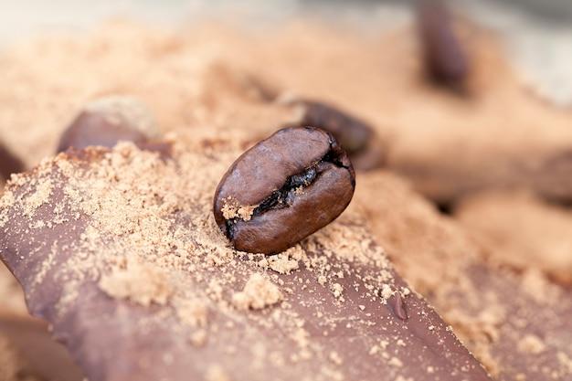 Produtos feitos de cacau e açúcar junto com ingredientes - cacau e café, quebrados em pedaços barra de chocolate doce com uma pitada de cacau e grãos de café