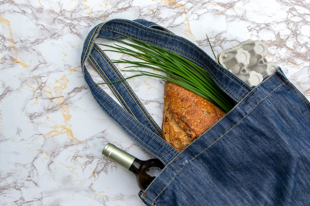 Produtos frescos no saco de mercado de jeans na mesa da cozinha em mármore