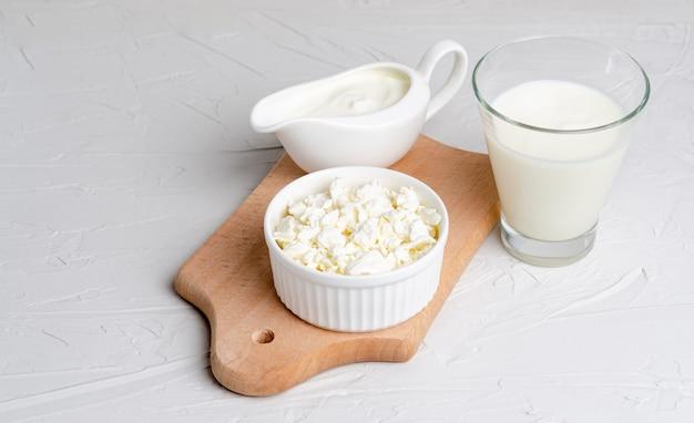 Produtos lácteos fermentados caseiros - kefir, creme de leite, queijo cottage em uma placa de madeira
