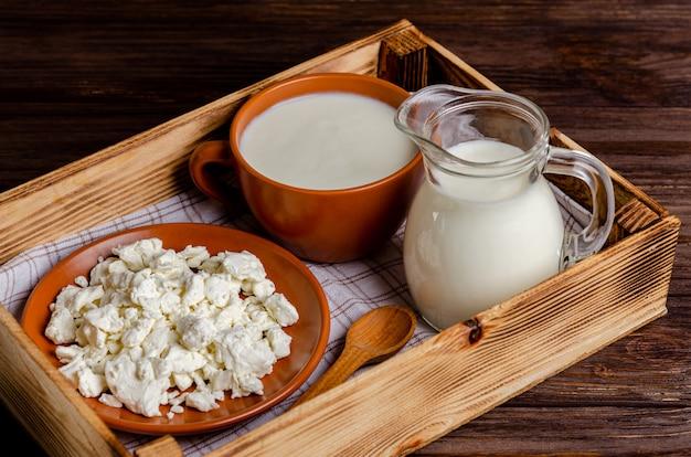 Produtos lácteos fermentados caseiros - kefir, queijo cottage em uma bandeja de madeira