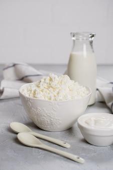 Produtos lácteos frescos do agricultor orgânico: leite, queijo cottage, creme de leite. na superfície de concreto cinza