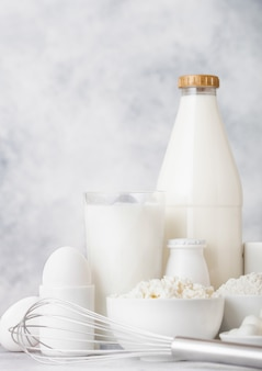 Produtos lácteos frescos. frasco de vidro de leite, tigela de creme de leite, queijo cottage e farinha e mussarela. ovos e queijo. batedor de aço