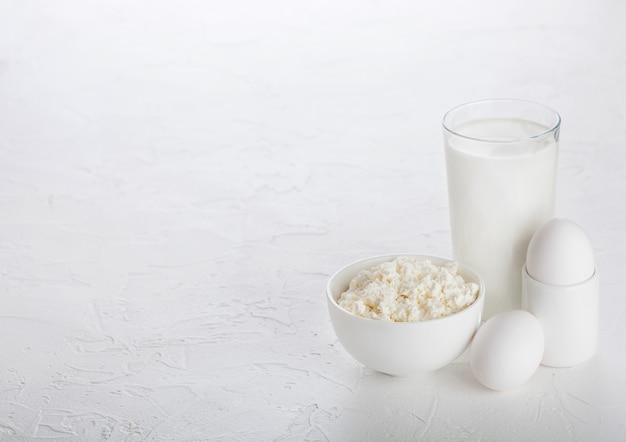 Produtos lácteos frescos na mesa branca. copo de leite, tigela de queijo e ovos.